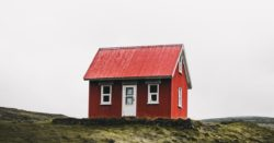 Freestanding red cabin on top of the hill