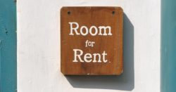 "Wooden board on a wall with the sign ""Room for rent"""